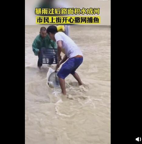 贵州平塘县暴雨路被淹 市民街头撒网捕鱼好欢乐